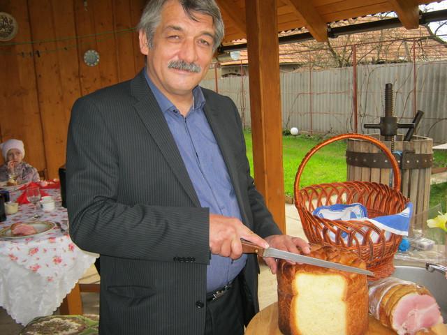 Муж нарезает пасхальный хлеб