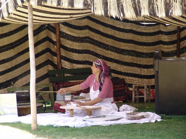 Женщина печет лепешки